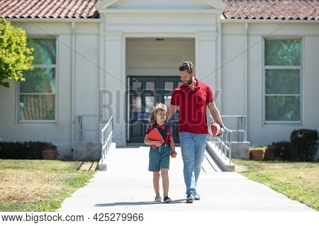 Father And Son Boy Walking Near School.