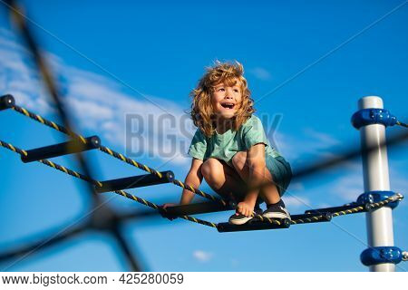 Cute Boy Climbs Up The Ladder On The Playground. Child Climbs Up The Ladder Against The Blue Sky. Co