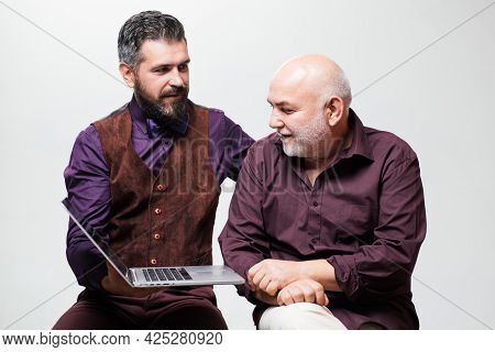 Adult Education. Happy Young Man With Senior Dad Have Fun Watching Funny Video On Laptop, Smiling El