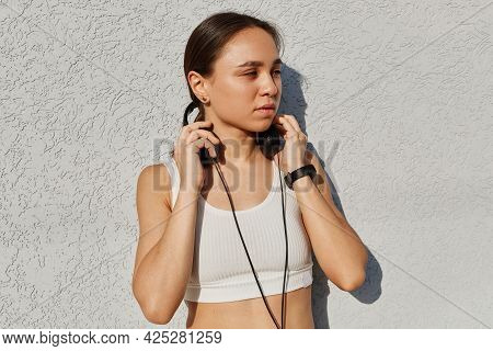 Outdoor Portrait Of Young Adult Beautiful Female Wearing White Top, Listening Music During Training,