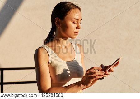 Portrait Of Young Attractive Sporty Woman In Stylish Sportwear Standing Near Gray Wall And Holding P