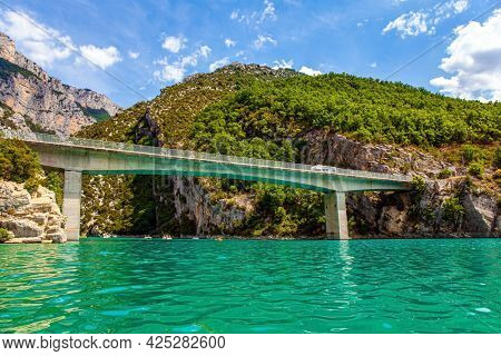 The bridge connects the banks of the canyon. The most beautiful and picturesque canyon in Europe - Verdon. French Alps. The walls of the gorge are overgrown with bushes.