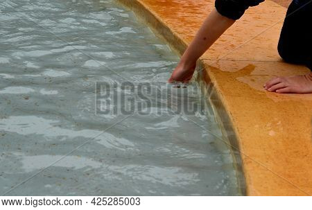Little Boy Soaks His Hands In The Fountain. The Wet Edge And Clear Water Invite You To Cool Off In A
