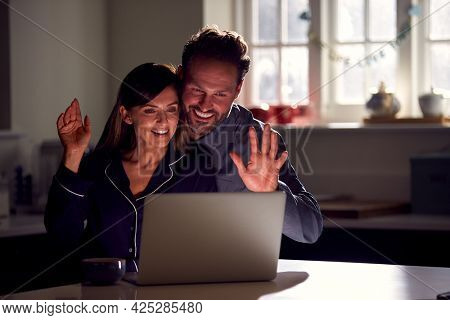 Couple Wearing Pyjamas Sitting In Kitchen At Night Using Laptop For Video Call