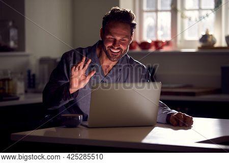 Man Wearing Pyjamas Sitting In Kitchen At Night Using Laptop For Video Call