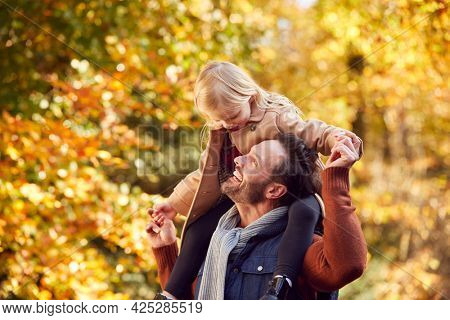 Father Playing Game Carrying Daughter On Shoulders On Family Walk Along Track In Autumn Countryside