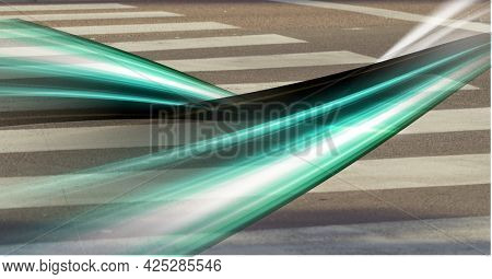 Green light trails against close up view of pedestrian crossing on the road. acceleration speed motion and technology concept