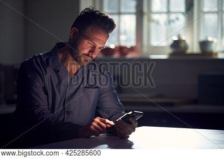 Man Wearing Pyjamas Sitting In Kitchen At Night Using Mobile Phone