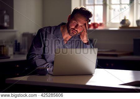 Unhappy Man Wearing Pyjamas Sitting In Kitchen At Night Using Laptop