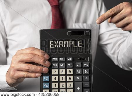 Example Word On Calculator Display In Male Hands Closeup.