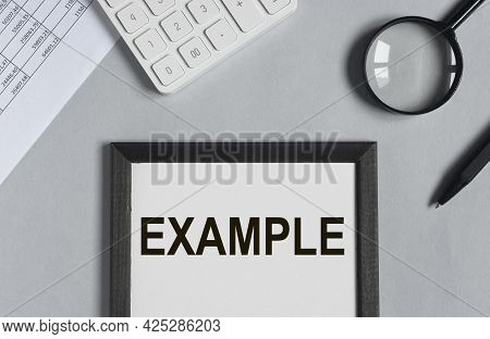 Example Word On Office Desk With Papers, Calculator And Magnify Glass, Top View.