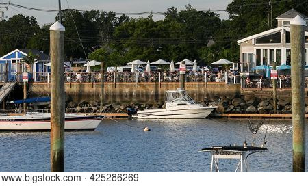 NORWALK, CT, USA - JUNE, 25, 2021: Evening lights and view from Veterans Park to   terrace with guests in Harbor Lights seafood restaurant