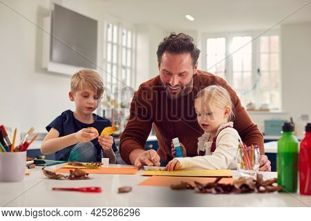 Father With Children At Home Doing Craft And Making Picture From Leaves In Kitchen