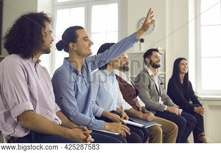 Man In The Audience Raises His Hand To Ask A Question During A Meeting With A Business Coach