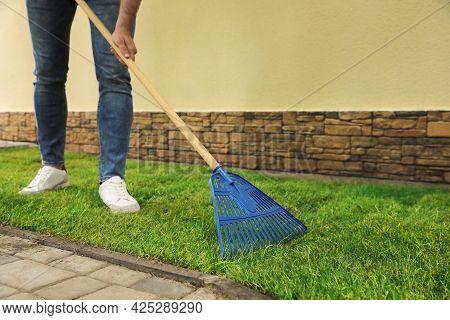 Young Man Raking Grass Sods At Backyard, Closeup