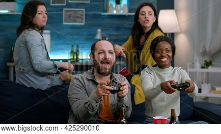 Woman With Blak Skin Playing Online Videogames With Man Friends For Gaming Competition Using Control