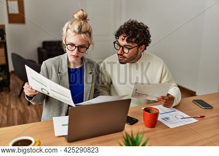 Two hispanic business workers concentrated working at the office.