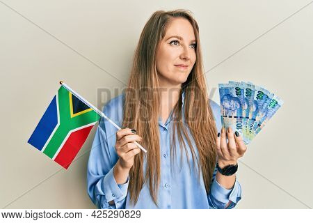 Young blonde woman holding south african flag and rands smiling looking to the side and staring away thinking.