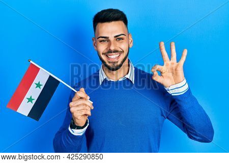 Young hispanic man with beard holding syria flag doing ok sign with fingers, smiling friendly gesturing excellent symbol