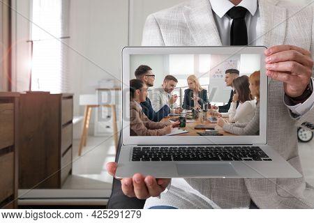 Businessman Attending Online Video Conference Via Modern Laptop Indoors, Closeup