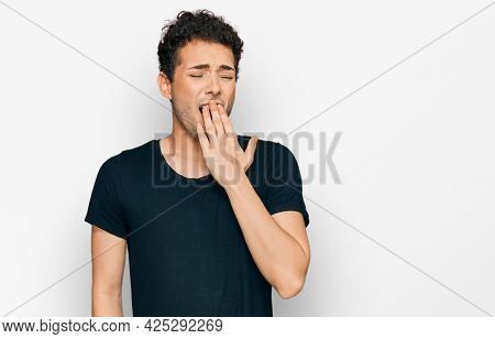 Young handsome man wearing casual black t shirt bored yawning tired covering mouth with hand. restless and sleepiness.