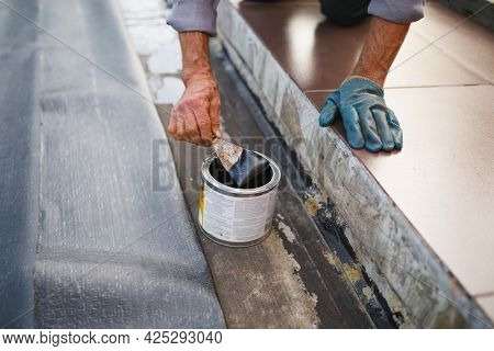 man working with waterproofing material, close-up view