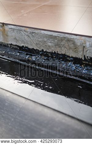 concrete seam waterproofing with bitumen, close-up view