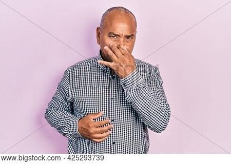 Middle age latin man wearing casual clothes smelling something stinky and disgusting, intolerable smell, holding breath with fingers on nose. bad smell