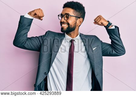 Handsome hispanic business man with beard wearing business suit and tie showing arms muscles smiling proud. fitness concept.