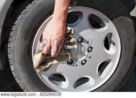 Hand Cleaning Car Wheel Rim With A Rag. Car Washing And Cleaning Concept.close Up View. Washing Serv