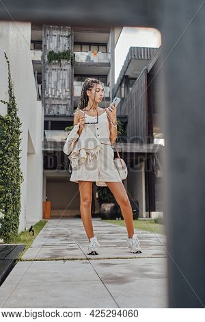 Stylish Woman With Phone Posing Against Mansion