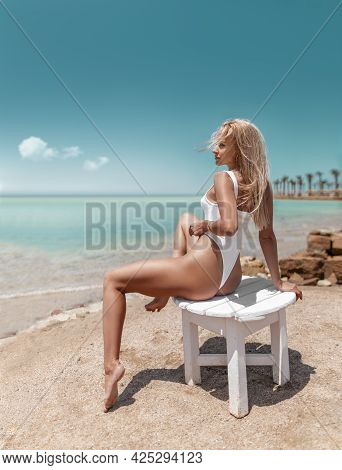 Beautiful Fitness Woman With Perfect Butt And Legs In White Swimwear Posing On The Ocean Beach Shore