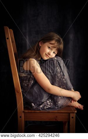 Full-length Portrait Of A Cute Fair-haired Caucasian Girl In A Dress Sitting On A Chair. Loneliness,