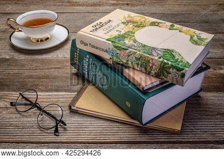 Fort Collins, CO, USA - March 8, 2020: Polish edition of several books by Olga Tokarczuk with tea and reading glasses - 2018 Nobel Prize in literature.