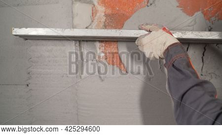 A Worker Plasters The Wall With A Spatula And Applies A Cement Mix Solution. The Repairman Lays The