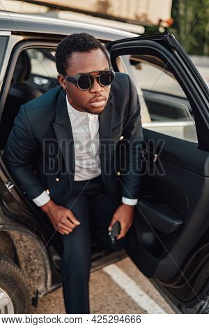 African Businessperson With Sunglasses Getting Out Of Car