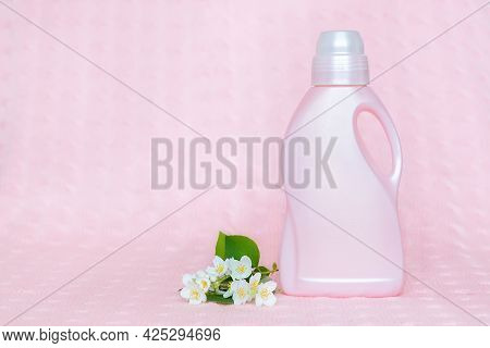 Pink Plastic Bottle With Laundry Detergent On A Soft Pink Background With Jasmine Flowers. Cleaning,