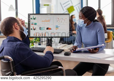 Paralysed Freelancer With Face Mask Discussing With Black Woman Partner Financial Problems, Checking