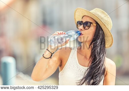 Young Attractive Woman Drinks Clear Water During A Hot Summer Day.