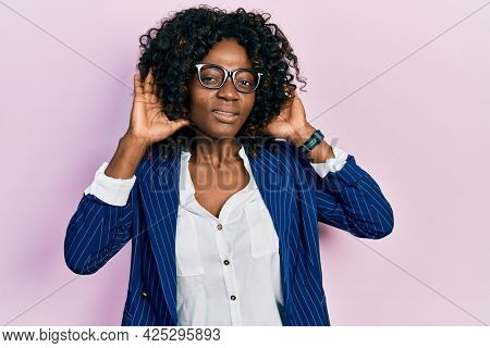 Young african american woman wearing business clothes and glasses trying to hear both hands on ear gesture, curious for gossip. hearing problem, deaf