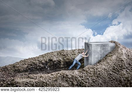 man pushes a huge concrete cube crawling into the ground. concept of determination and strength.