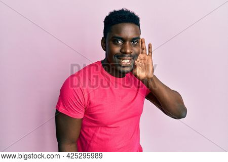 Handsome black man wearing casual pink t shirt smiling with hand over ear listening and hearing to rumor or gossip. deafness concept.