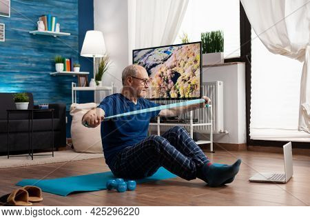 Pensioner Working At Body Resistance Exercising Arms Muscles Using Elastic Band Sitting On Yoga Mat