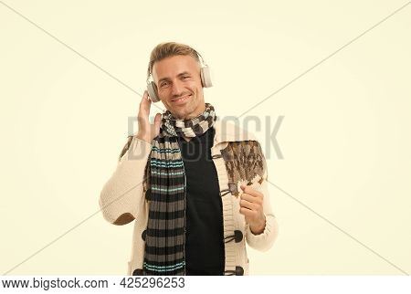 Bearded Man In Knitted Winter Clothes. Warm Wear For Cold Season. Handsome Guy In Sweater Listen Mus
