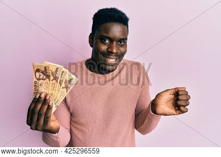 Handsome black man holding 5000 hungarian forint banknotes screaming proud, celebrating victory and success very excited with raised arm