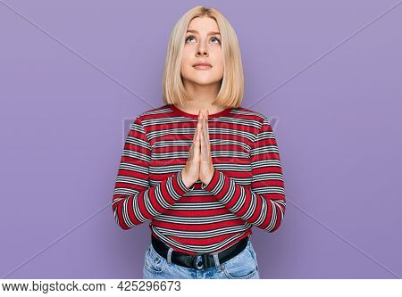 Young blonde woman wearing casual clothes begging and praying with hands together with hope expression on face very emotional and worried. begging.