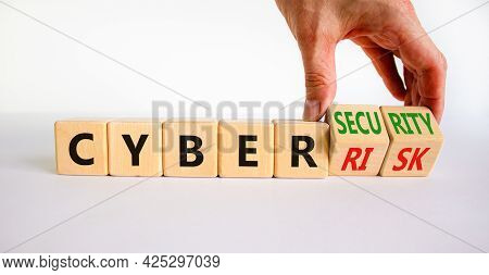 Cyber-security Vs Cyber-risk Symbol. Businessman Turns Wooden Cubes, Changes Words Cyber-risk To Cyb