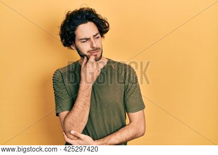 Handsome hispanic man wearing casual green t shirt thinking concentrated about doubt with finger on chin and looking up wondering