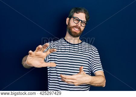 Caucasian man with beard wearing striped t shirt and glasses disgusted expression, displeased and fearful doing disgust face because aversion reaction. with hands raised
