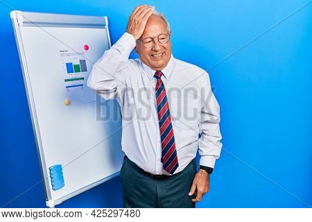 Senior man with grey hair standing by business blackboard smiling confident touching hair with hand up gesture, posing attractive and fashionable